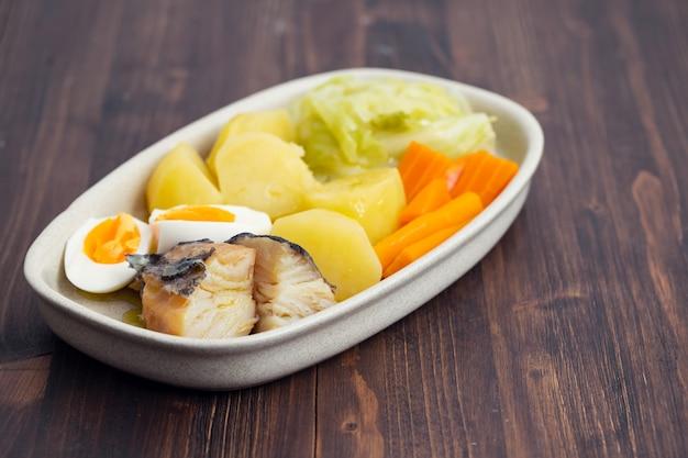 Kabeljau mit gekochtem ei und gemüse auf teller