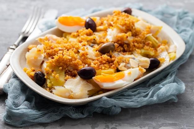 Kabeljau mit süßkartoffel, gekochtem ei, oliven und maisbrot auf weißem teller