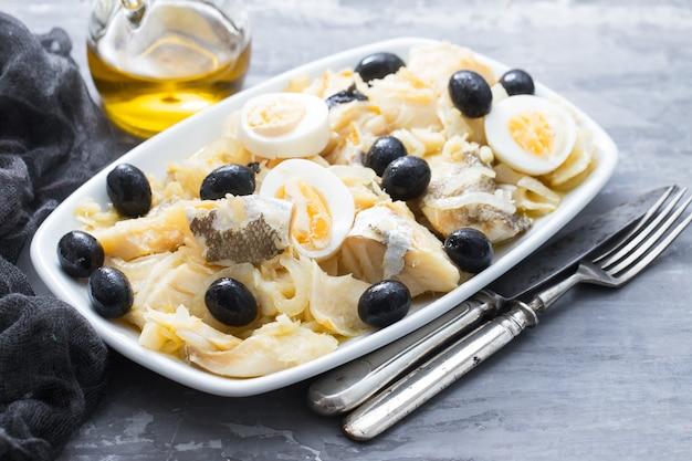 Kabeljau mit zwiebeln, oliven, eiern und olivenöl auf keramikschale
