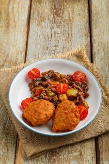 Kabeljaukoteletts mit gedünsteten kartoffeln und gemüse auf einem teller auf einer serviette auf dem tisch. vertikales foto