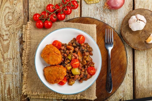 Kabeljaukoteletts mit kartoffeln und gemüse auf einem runden brett in der nähe von zutaten.