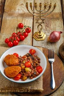 Kabeljaukoteletts mit kartoffeln und gemüse neben menora und zutaten. vertikales foto