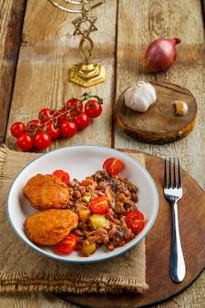 Kabeljaukoteletts mit kartoffeln und gemüse neben menora und zutaten.