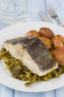 Kabeljaus mit kartoffel und gemüse auf weißer platte und glas wasser auf purpleheart