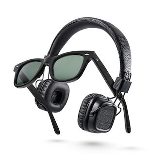 Kabellose schwarze on-ear-kopfhörer und plastiksonnenbrille auf weißem hintergrund