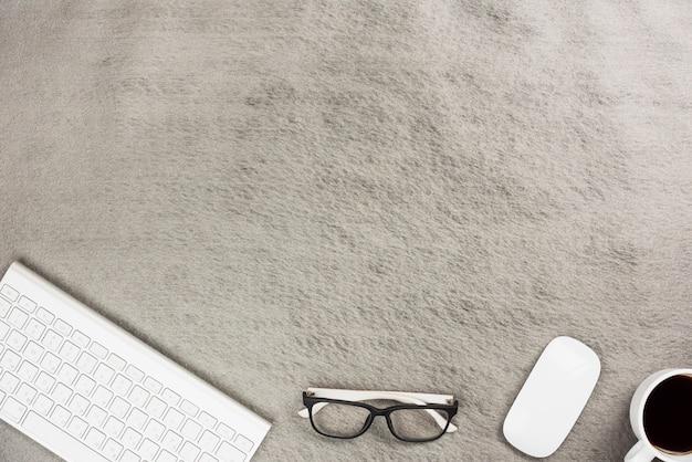 Kabellose tastatur; maus; brillen und kaffeetasse auf grauem schreibtisch