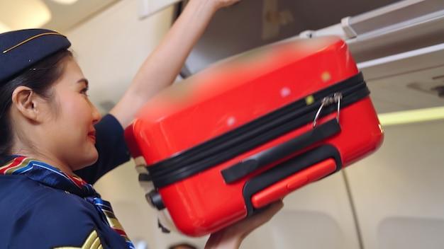 Kabinenpersonal heben gepäcktasche im flugzeug an. konzept für flugverkehr und tourismus.