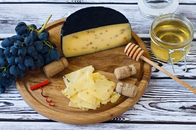 Kachota-käse auf einem hölzernen brett auf einem hölzernen hintergrund mit wein in einem glas