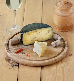 Kachotta-käse auf einem hölzernen brett auf einem hölzernen hintergrund mit wein in einem glas und in einem honig