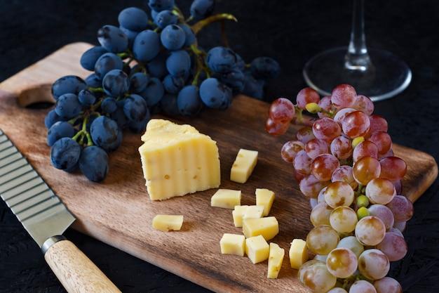 Kachotta-käse auf einem hölzernen brett mit trauben auf einem schwarzen hintergrund