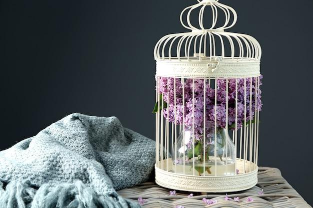Käfig mit schönem blühendem flieder auf tisch gegen farbe