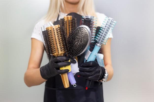 Kämme zum stylen in weiblichen händen. professionelle friseurwerkzeuge, ausrüstung.