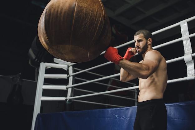 Kämpfer, der einige tritte mit boxsack übt kick-boxsack auf dunklem hintergrund schwarzer boxsack wiegt im fitnessstudio hochwertige k-aufnahmen