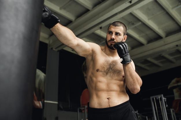 Kämpfer, der einige tritte mit boxsack übt. kick, boxsack auf dunklem hintergrund. schwarzer boxsack wiegt im fitnessstudio. hochwertiges 4k-filmmaterial