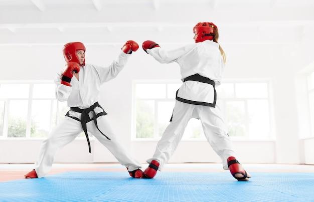 Kämpfer, der in der speziellen roten schutzausrüstung für kampf, zusammen boxend trägt.