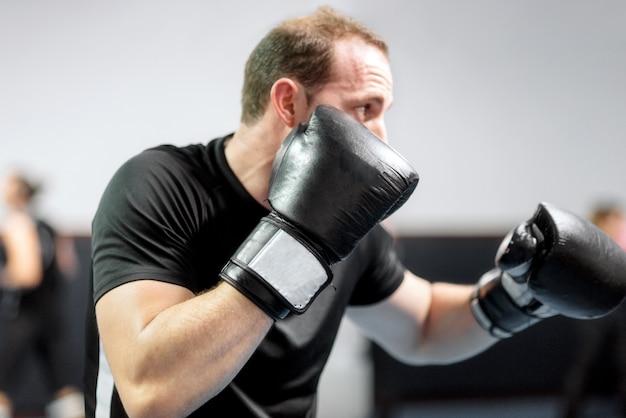 Kämpfer des jungen mannes, kickboxen mit seinem trainer ausbildend und kämpfen im ring.