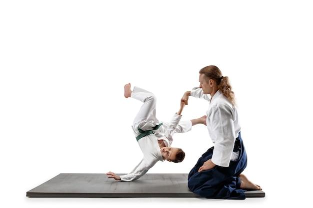 Kämpfer im weißen kimono auf schwarzem tatami