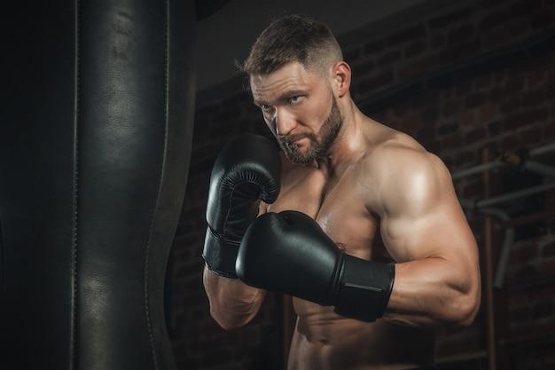 Kämpfer mit aggression schlägt boxsack