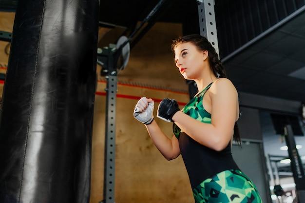 Kämpferin im fitnessstudio bereit, mit boxsack zu arbeiten. fitnessmodel.