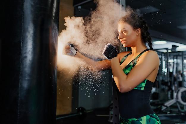Kämpferin, schlägt selbstbewusst eine birne im fitnessstudio. frau macht starken tritt. crossfit. fitnessmodel.