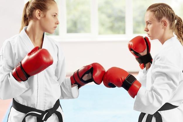 Kämpferin zwei, die in der position bereit steht, kampf gegen großes fenster zu beginnen.