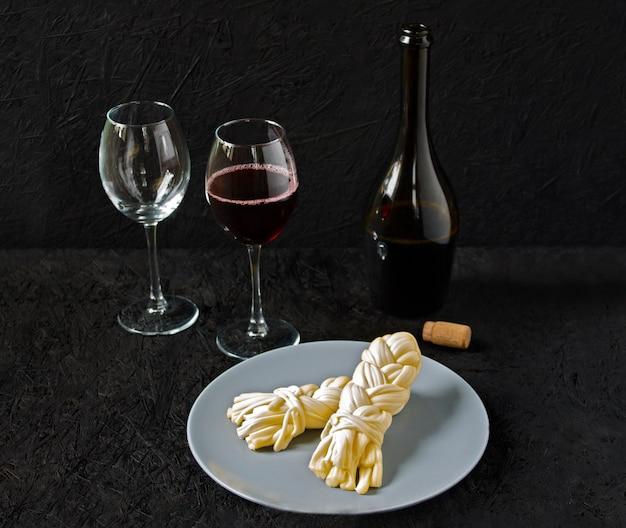 Käse auf einer platte und wein auf einem schwarzen hintergrund. sulguni-käse