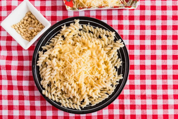 Käse auf frischen teigwaren nahe platte mit nüssen auf tabelle