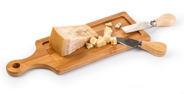 Käse auf schneidebrett mit messer lokalisiert auf weiß