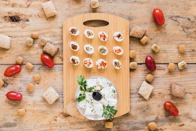 Käse auf schneidebrett mit tomaten und gebäck auf dem schreibtisch