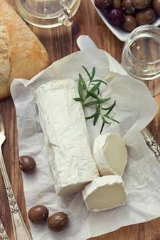 Käse auf weißem papier, glas weißwein, oliven und brot