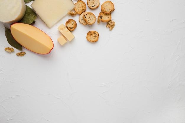 Käse; brotscheibe und walnuss über weiße strukturierte oberfläche