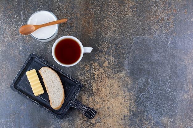 Käse, butter auf einer schwarzen platte mit einer tasse tee und sahne