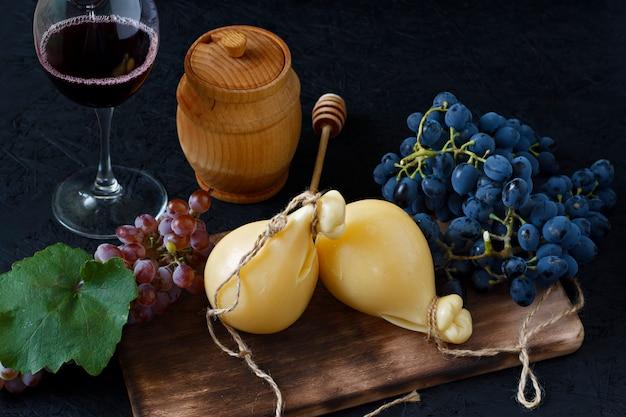 Käse caciocavallo auf einem hölzernen brett mit trauben, honig und wein auf einem schwarzen hintergrund. käse birne