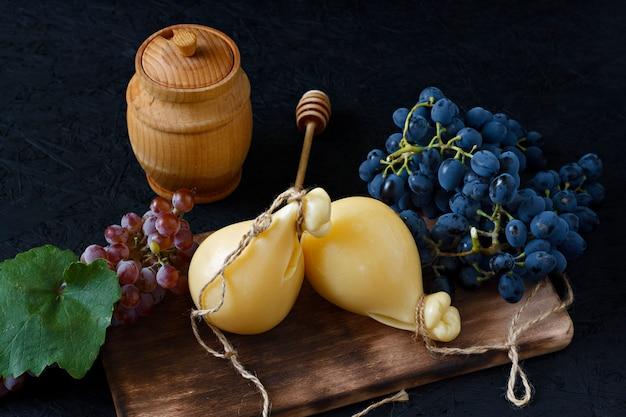 Käse caciocavallo auf einem hölzernen brett mit trauben und honig auf einem schwarzen hintergrund. käse birne