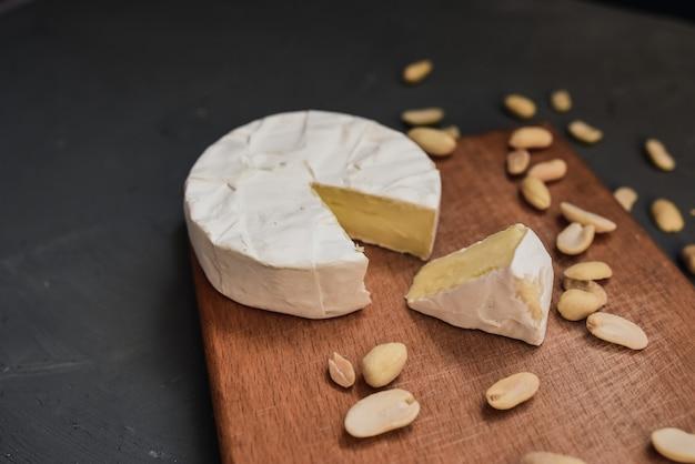 Käse-camembert mit schimmel und nüssen auf dem holzschneidebrett
