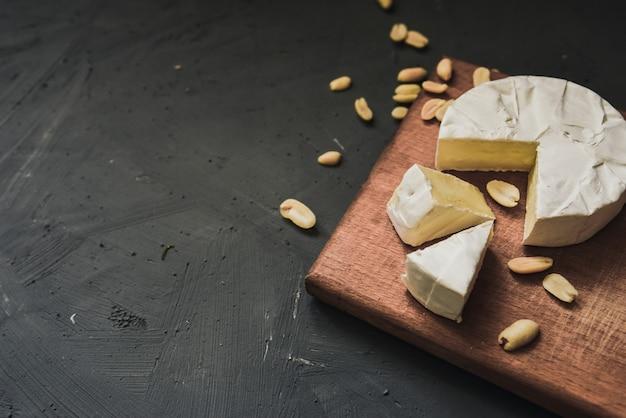 Käse camembert mit schimmel und nüssen auf holz