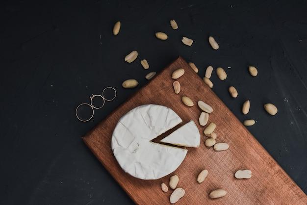 Käse-camembert mit schimmel und nüssen und eheringen auf dem hölzernen schneidebrett