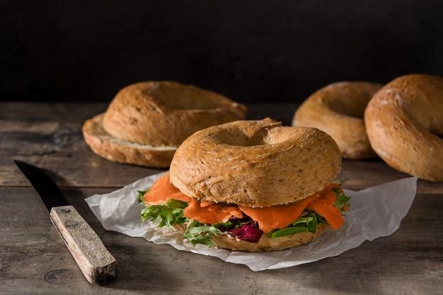 Käse des bagelsandwiches mit sahne, geräucherter lachs und gemüse auf holztisch
