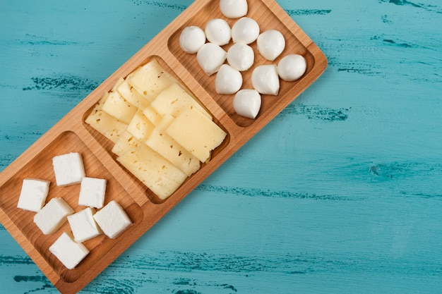 Käse-fachgericht mit verschiedenen käsesorten, auf rustikalem holztisch