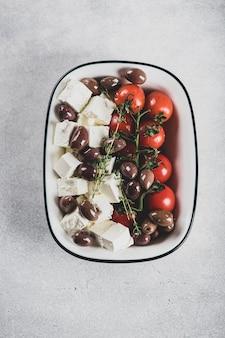 Käse feta, olivenöl, kalamata-oliven und kirschtomaten zum backen, ansicht von oben