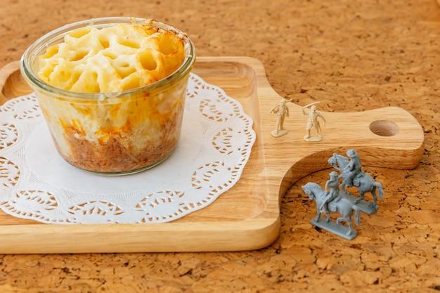 Käse gebackenes penne in der glasschüssel auf hölzerner platte mit miniatursoldaten und cowboys, die pferde reiten.