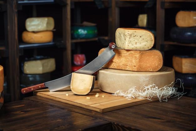 Käse geht mit scheiben und messern auf einem hölzernen brett mit einem innenraum voran
