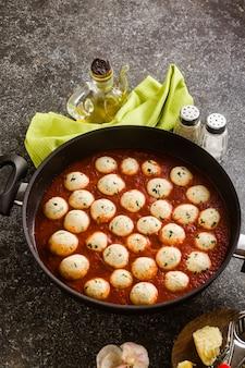 Käse-gemüse-ricotta-fleischbällchen in tomatensauce in einer pfanne. traditionelle italienische küche für die ganze familie, party oder restaurantmenü