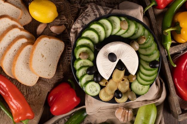 Käse-, gurken- und olivenplatte mit geschnittenem weißbrot. draufsicht