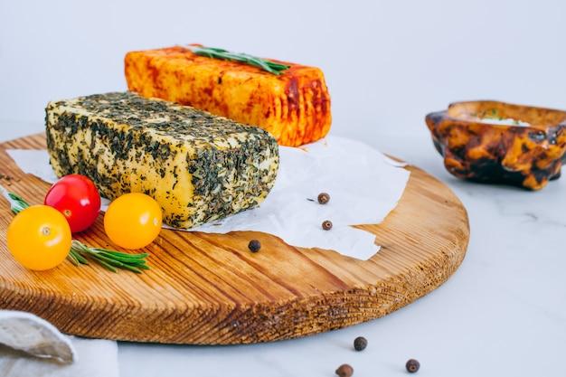Käse halumi mit minze und geräuchertem paprika auf einem holzbrett mit tomaten
