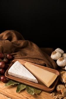 Käse, knoblauch, trauben und lorbeerblätter auf hölzerner arbeitsplatte gegen schwarzen hintergrund