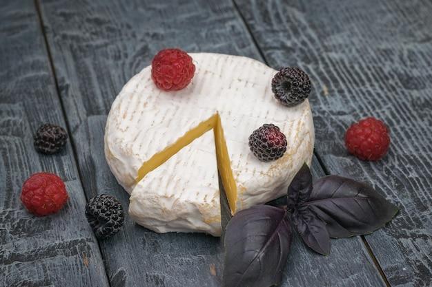 Käse mit beeren und blauen basilikumblättern auf einem holzstamm.