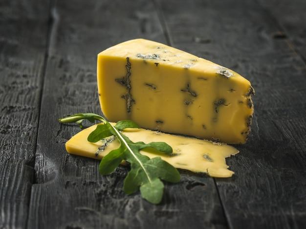 Käse mit blauem schimmel und einem stück rucola auf einem holztisch schneiden. käsespezialität. eine nützliche form