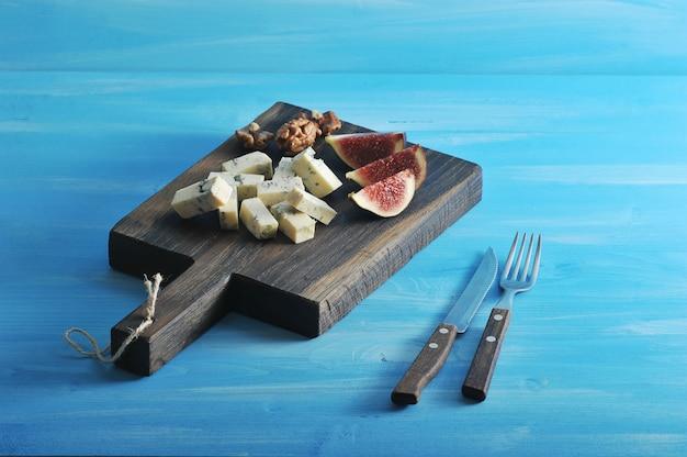 Käse mit blauschimmel dorblu auf einem hölzernen brett. um den geschmack des käses zu mildern, wurden scheiben reifer feigen und walnüsse hinzugefügt.