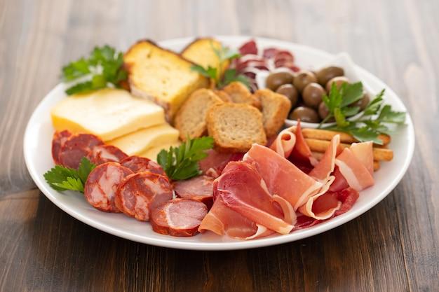 Käse mit geräuchertem fleisch auf weißem teller